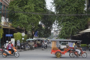 a Tuk Tuk sputters past a lane in Phenom Penh